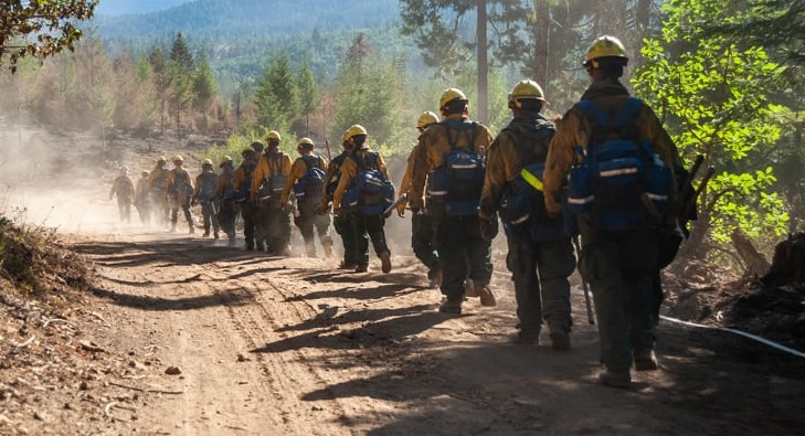 fire fighters walking on a dirt road