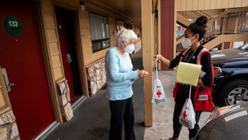 Woman from Red Cross hands elderly woman a bag of supplies outside a hotel room