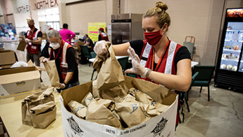 Woman Red Cross relief worker fills emergency food boxes for wildfire evacuees
