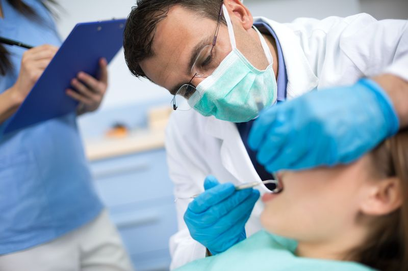 Dentist wearing mask and gloves while doing a procedure